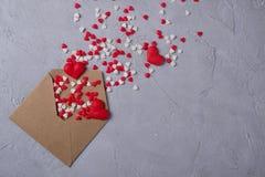 Πολύχρωμη μύγα καρδιών καραμελών ζάχαρης γλυκών από τον ταχυδρομικό φάκελο εγγράφου τεχνών Ευτυχής έννοια ημέρας βαλεντίνων ` s Στοκ εικόνες με δικαίωμα ελεύθερης χρήσης
