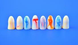 πολύχρωμη στάση earplugs στη σειρά σε ένα μπλε υπόβαθρο στοκ εικόνες