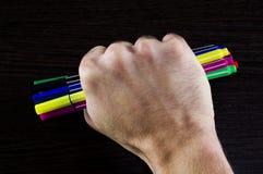 Πολύχρωμοι δείκτες σε ένα χέρι σε έναν σκοτεινό πίνακα υποβάθρου Στοκ Εικόνες
