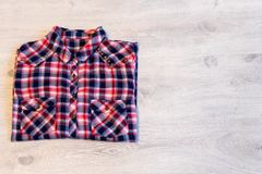 Πολύχρωμο ελεγμένο να βρεθεί πουκάμισων γυναικών ` s που διπλώνεται τακτοποιημένα σε ένα λ Στοκ εικόνα με δικαίωμα ελεύθερης χρήσης