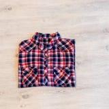 Πολύχρωμο ελεγμένο να βρεθεί πουκάμισων γυναικών ` s που διπλώνεται τακτοποιημένα σε ένα λ Στοκ Φωτογραφία