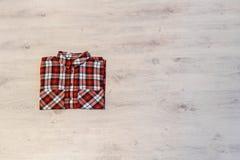 Πολύχρωμο ελεγμένο να βρεθεί πουκάμισων γυναικών ` s που διπλώνεται τακτοποιημένα σε ένα λ Στοκ Εικόνες