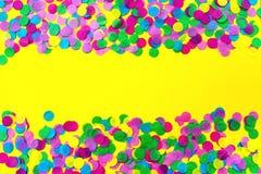 Πολύχρωμο κομφετί σε ένα κίτρινο υπόβαθρο r στοκ φωτογραφίες