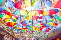 Πολύχρωμο υπόβαθρο ομπρελών Ζωηρόχρωμες ομπρέλες που επιπλέουν επάνω από την οδό Διακόσμηση οδών στοκ φωτογραφίες