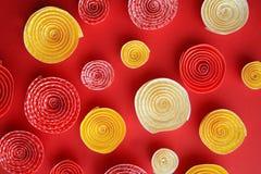 Πολύ έγγραφο κινείται σπειροειδώς κίτρινος και πορτοκαλής σε ένα κόκκινο υπόβαθρο Στοκ εικόνες με δικαίωμα ελεύθερης χρήσης