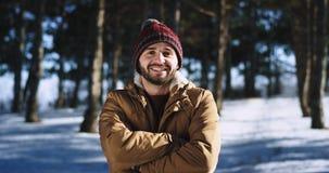 Πολύ ελκυστικό άτομο με ένα μεγάλο χαμόγελο που φαίνεται ευθύ στη κάμερα και αίσθημα συγκινημένο στέκεται στη μέση φιλμ μικρού μήκους