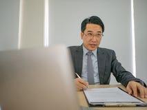 Πολύ ευτυχές ασιατικό επιχειρησιακό άτομο στο γραφείο στοκ φωτογραφία με δικαίωμα ελεύθερης χρήσης