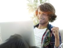 Πολύ ευτυχής τύπος με μια συνεδρίαση lap-top κοντά σε ένα τραπεζάκι σαλονιού Στοκ Φωτογραφία