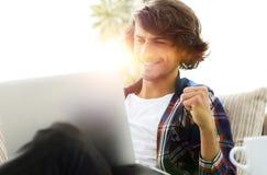 Πολύ ευτυχής τύπος με μια συνεδρίαση lap-top κοντά σε ένα τραπεζάκι σαλονιού Στοκ φωτογραφίες με δικαίωμα ελεύθερης χρήσης