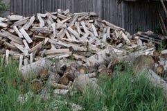 Πολύ καυσόξυλο που βρίσκεται στο ναυπηγείο ενός του χωριού σπιτιού στη χλόη Στοκ φωτογραφία με δικαίωμα ελεύθερης χρήσης