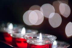 Πολύ κόκκινο κερί κεριών στο γυαλί με το όμορφο bokeh στο υπόβαθρο Κινηματογράφηση σε πρώτο πλάνο Στοκ Εικόνες