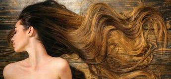 Πολύ μακρυμάλλης στο ξύλινο υπόβαθρο Όμορφο πρότυπο με το σγουρό hairstyle Έννοια κομμωτηρίων Προσοχή και προϊόντα τρίχας στοκ εικόνες