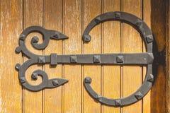 Πολύ μεγάλη άρθρωση σιδήρου που σφυρηλατείται σε μια ξύλινη πόρτα στο χρησιμοποιημένο χρώμα Στοκ φωτογραφίες με δικαίωμα ελεύθερης χρήσης