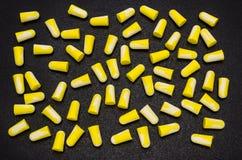 Πολύ να βρεθεί earplugs, για την προστασία ενάντια στο θόρυβο σε κίτρινο και το λευκό, που απομονώνεται σε ένα μαύρο υπόβαθρο με  στοκ φωτογραφίες
