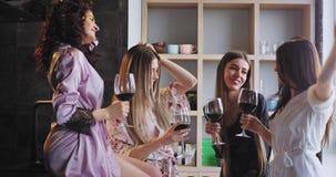 Πολύ φιλική ομάδα ελκυστικών κυριών στις πυτζάμες που απολαμβάνουν το χρόνο μαζί ενώ πίνοντας κρασί και που ξοδεύουν ένα αγαθό απόθεμα βίντεο