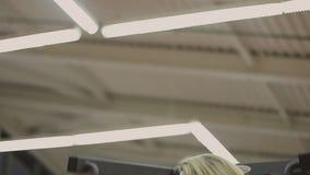 Πολύ όμορφα θηλυκά τραίνα εκπαιδευτών σε μια μηχανή ικανότητας σε μια λέσχη ικανότητας απόθεμα βίντεο