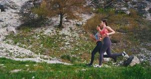 Πολύ όμορφες νέες κυρίες που τρέχουν σκληρά μέσω του δρόμου βουνών σε μια ηλιόλουστη ημέρα τις που ασκούν ένα σκληρό workout με τ απόθεμα βίντεο