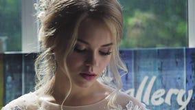Πολύ όμορφος ξανθός με τα μπλε μάτια και τα υπόβαθρα και τις εικόνες παραθύρων απόθεμα βίντεο