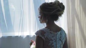 Πολύ όμορφος ξανθός με τα μπλε μάτια σε ένα άσπρο φόρεμα νυφών κοντά σε ένα παράθυρο με μια ανθοδέσμη των λουλουδιών φιλμ μικρού μήκους