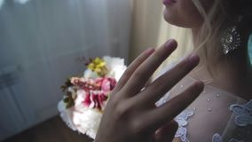 Πολύ όμορφος ξανθός με τα μπλε μάτια σε ένα άσπρο φόρεμα νυφών κοντά σε ένα παράθυρο με μια ανθοδέσμη των λουλουδιών απόθεμα βίντεο