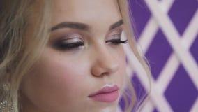 Πολύ όμορφος ξανθός με τα μπλε μάτια στο άσπρο φόρεμα νυφών στο πορφυρό υπόβαθρο στο στούντιο απόθεμα βίντεο