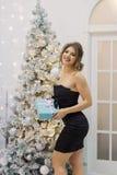 Πολύ όμορφο και ευτυχές κορίτσι που στέκεται κοντά στο χριστουγεννιάτικο δέντρο με το δώρο ενός νέου έτους στοκ φωτογραφία με δικαίωμα ελεύθερης χρήσης