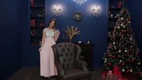 Πολύ όμορφο κορίτσι με ένα ποτήρι της σαμπάνιας στο ντεκόρ του νέου έτους απόθεμα βίντεο
