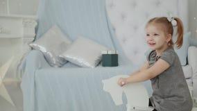 Πολύ όμορφο μικρό κορίτσι που οδηγά σε ένα ξύλινο άλογο στο δωμάτιο και το χαμόγελο του νέου έτους φιλμ μικρού μήκους
