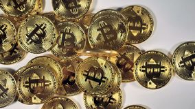 Πολύ Bitcoins σε ένα άσπρο υπόβαθρο Κινηματογράφηση σε πρώτο πλάνο απόθεμα βίντεο