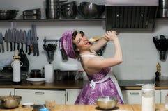Πονηρό όμορφο κορίτσι με τους μάγειρες makeup στην κουζίνα Στοκ φωτογραφία με δικαίωμα ελεύθερης χρήσης