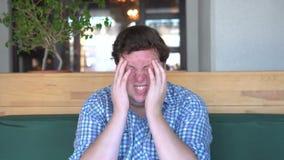 Πονοκέφαλος ή ημικρανία Ένα νέο παχύ άτομο κρατά τα χέρια του πίσω από το κεφάλι του απόθεμα βίντεο