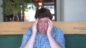 Πονοκέφαλος ή ημικρανία Ένα νέο παχύ άτομο κρατά τα χέρια του πίσω από το κεφάλι του φιλμ μικρού μήκους