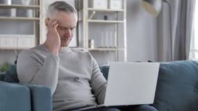 Πονοκέφαλος, κουρασμένο γκρίζο άτομο τρίχας που χρησιμοποιεί το lap-top απόθεμα βίντεο