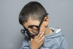 Πονοκέφαλος, σκοτεινός-μαλλιαρός νέος σπουδαστής με τα μεγάλα γυαλιά που σκέφτονται τη Γερμανία Στοκ φωτογραφία με δικαίωμα ελεύθερης χρήσης