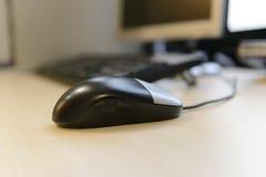 Ποντίκι υπολογιστών κινηματογραφήσεων σε πρώτο πλάνο πριν από τον υπολογιστή γραφείου υπολογιστών στο καφετί ξύλινο γραφείο Στοκ Εικόνες