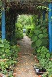 Πορεία κήπων με την υπερυψωμένη αψίδα των αμπέλων που οδηγούν στο προαύλιο στοκ φωτογραφία με δικαίωμα ελεύθερης χρήσης