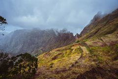 Πορεία οδοιπορίας κατά μήκος της άκρης βουνών που εισβάλλεται με τη verdant χλόη Οι αιχμές βουνών καλύπτονται από την ομίχλη Κοιλ Στοκ φωτογραφία με δικαίωμα ελεύθερης χρήσης