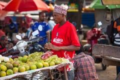 Πορτοκάλια αποφλοίωσης ατόμων στην τοπική αγορά στοκ εικόνα με δικαίωμα ελεύθερης χρήσης