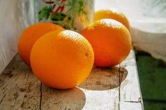Πορτοκάλια σε μια ξύλινη στρωματοειδή φλέβα παραθύρων στοκ εικόνα
