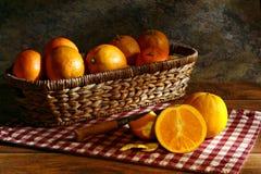 Πορτοκάλια στο αγροτικό καλάθι στην εκλεκτής ποιότητας ακόμα ζωή Στοκ εικόνες με δικαίωμα ελεύθερης χρήσης