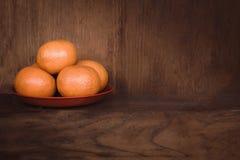 Πορτοκάλια στο κόκκινο πιάτο με το ξύλινο διάστημα υποβάθρου και αντιγράφων στοκ φωτογραφίες