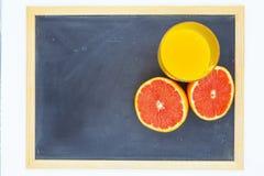 Πορτοκάλι ή γκρέιπφρουτ κοντά σε ένα ποτήρι του χυμού από πορτοκάλι στοκ εικόνες