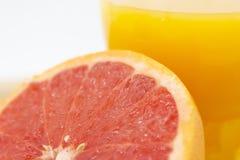 Πορτοκάλι ή γκρέιπφρουτ κοντά σε ένα ποτήρι του χυμού από πορτοκάλι στοκ φωτογραφία