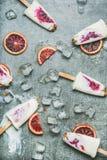 Πορτοκάλι αίματος, γιαούρτι και granola popsicles στον πάγο, γκρίζο υπόβαθρο Στοκ εικόνες με δικαίωμα ελεύθερης χρήσης