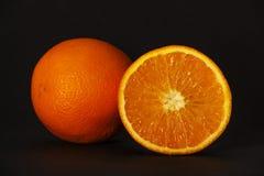 Πορτοκάλι, ολόκληρο ένα πορτοκαλί, μισό πορτοκάλι, που απομονώνεται σε ένα μαύρο υπόβαθρο Μπροστινή όψη διάστημα αντιγράφων Υγιής Στοκ Εικόνες