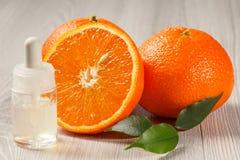 Πορτοκάλι περικοπών με δύο ολόκληρα πορτοκάλια και μπουκάλι με το aromatherapy ο Στοκ φωτογραφία με δικαίωμα ελεύθερης χρήσης