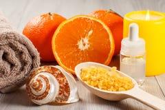 Πορτοκάλι περικοπών με δύο ολόκληρα πορτοκάλια, πετσέτα, κοχύλι θάλασσας, μπουκάλι με Στοκ εικόνες με δικαίωμα ελεύθερης χρήσης