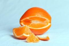 Πορτοκάλι που κόβεται στα κομμάτια σε ένα γαλαζωπό υπόβαθρο στοκ φωτογραφία με δικαίωμα ελεύθερης χρήσης