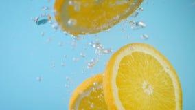 Πορτοκάλι που τεμαχίζεται φρέσκο με τις αεροφυσαλίδες που εμπίπτουν στο νερό απόθεμα βίντεο