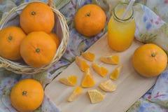 Πορτοκάλι σε ένα ξύλινο καλάθι και χυμός σε ένα υπόβαθρο υφασμάτων στοκ φωτογραφία